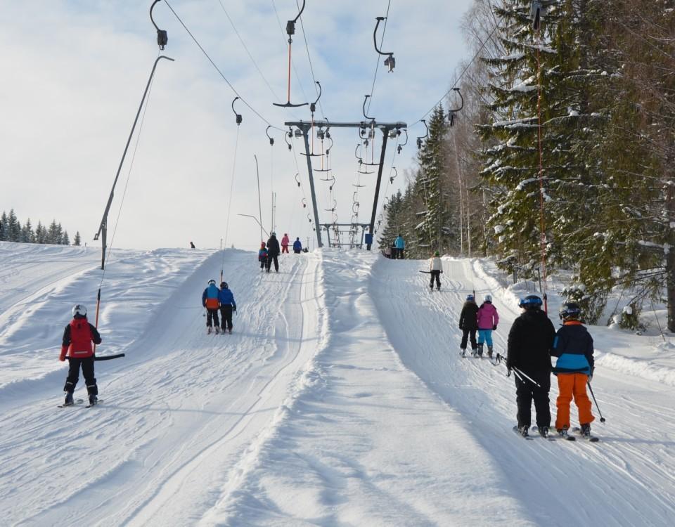 Snöig slalombacke med människor.