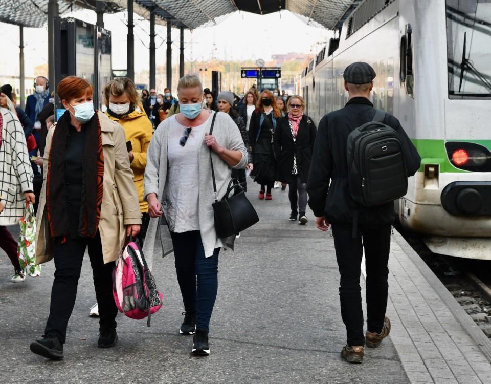 människor på en tågperrong med munskydd