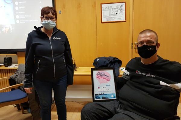 kvinna och man med munskydd och ett tillgänglighetsdiplom