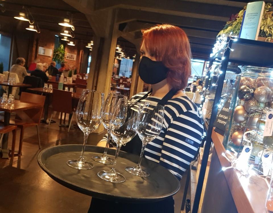 en kvinna med en bricka med glas i en restaurang