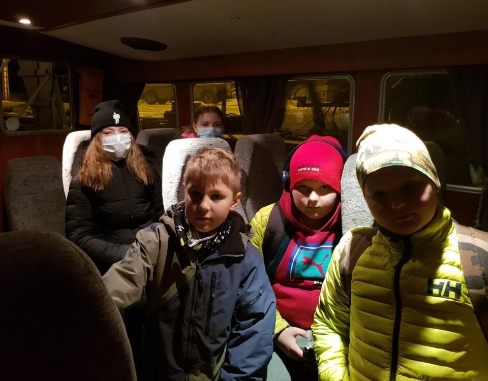 Fem skolelever i en passagerarbåt. Mörkt.