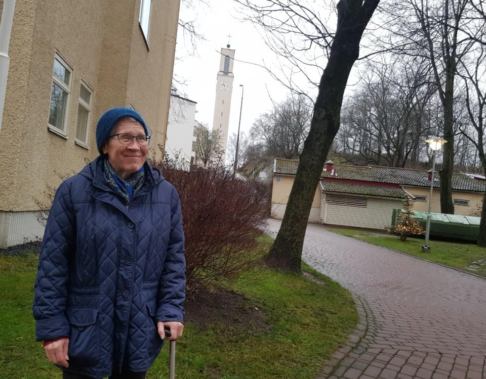 en äldre kvinna framför en kyrka