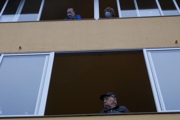några personer tittar ut från sina balkonger