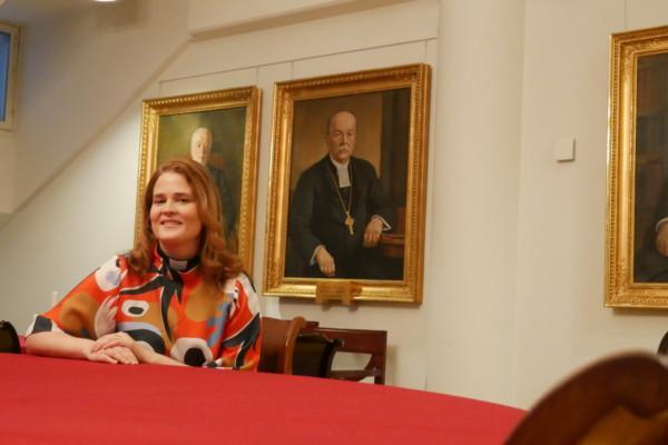 en kvinna sitter vid ett bord med en röd duk, i bakgrunden målade portrtätt av äldre, manliga präster
