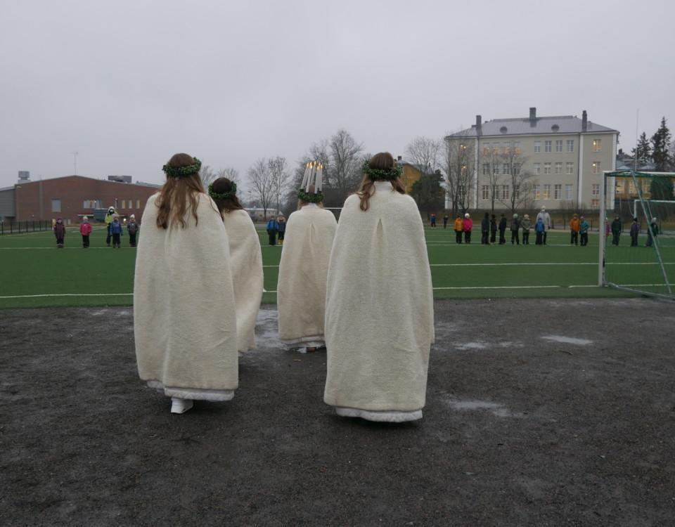 ett litet luciatåg bakifrån sett, går mot en sportplan i grått väder