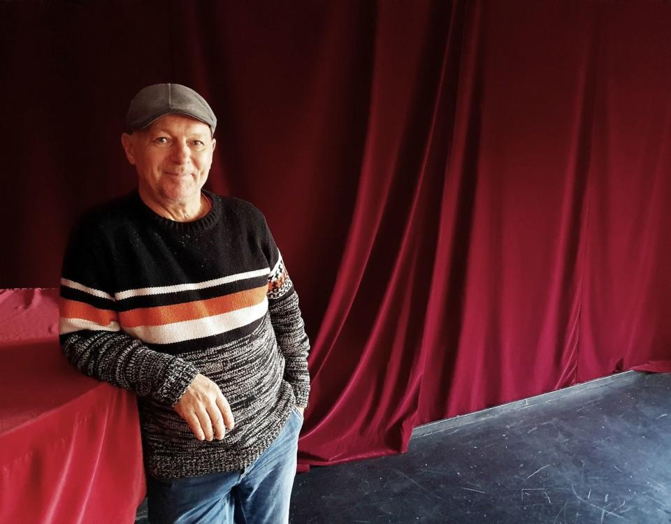 Österlund iklädd en stickad tröja och gammaldags keps står lutad mot ett övertäckt piano.