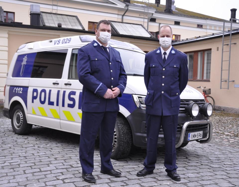 två poliser framför en bil