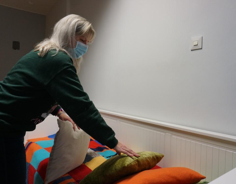 en kvinna med munskydd bäddar en säng