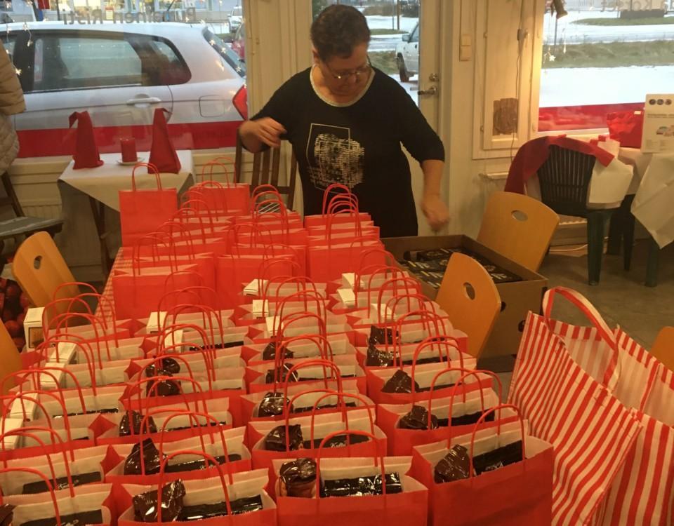 Dam med en stor mängd röda presentpåsar på ett bord framför sig