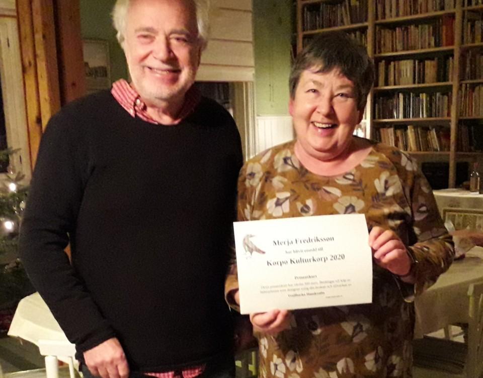en leende man och kvinna står bredvid varann, kvinnan håller upp ett diplom