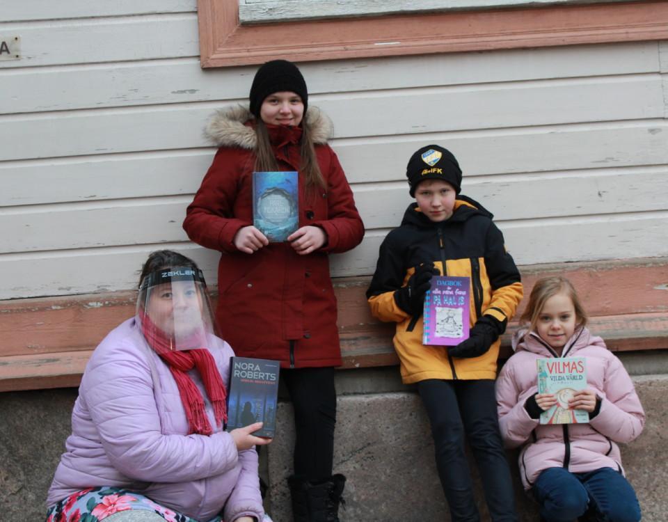 skolelever håller upp böcker