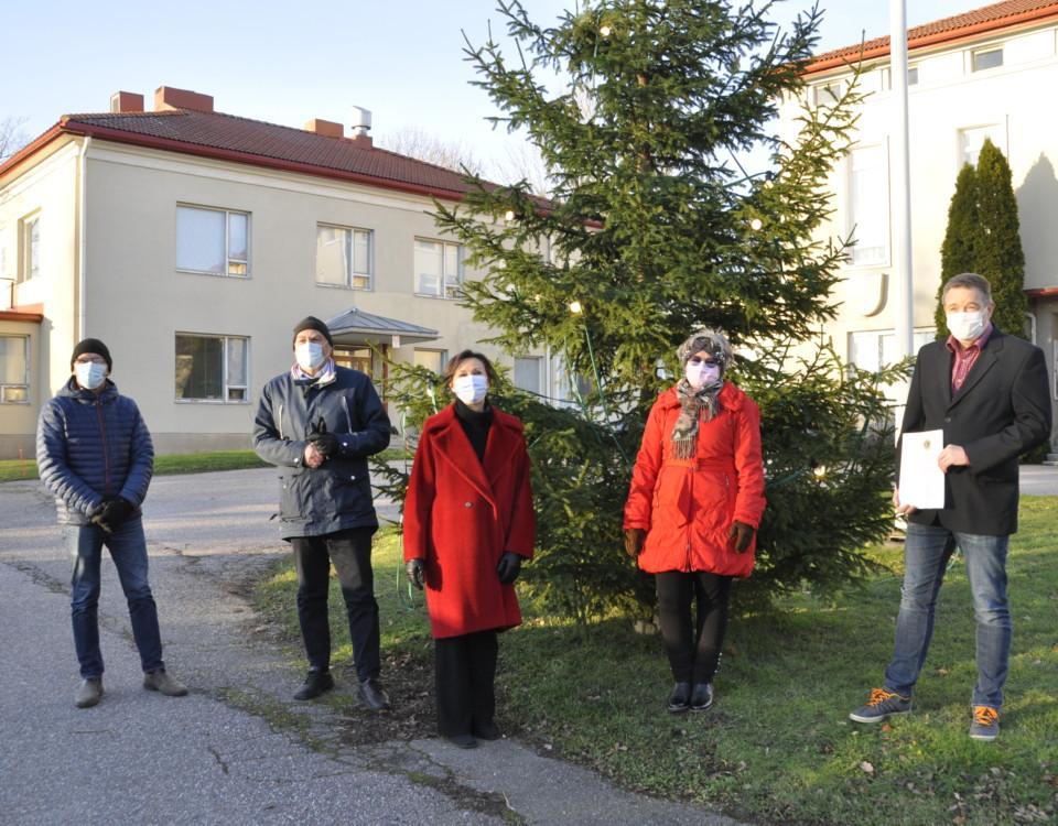 Fwm personer på en gräsmatta vid en julgran