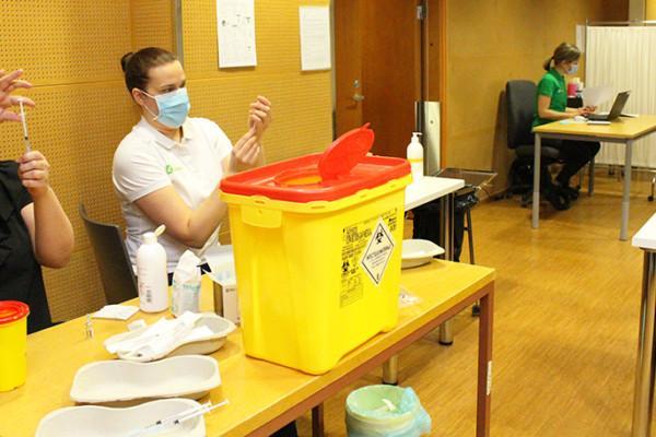 personer vid bord förbereder vacciner