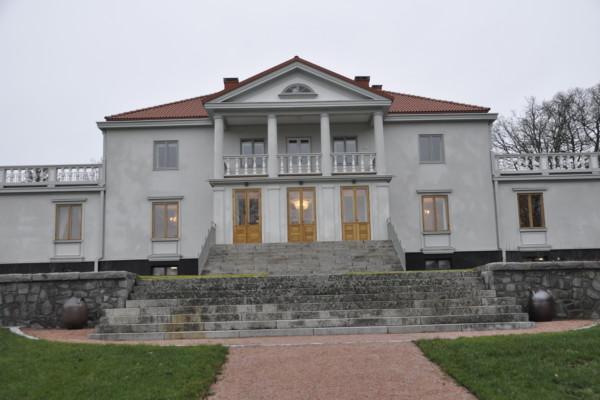 Ståtlig, vit karaktärsbyggnad i två våningar med två flyglar.