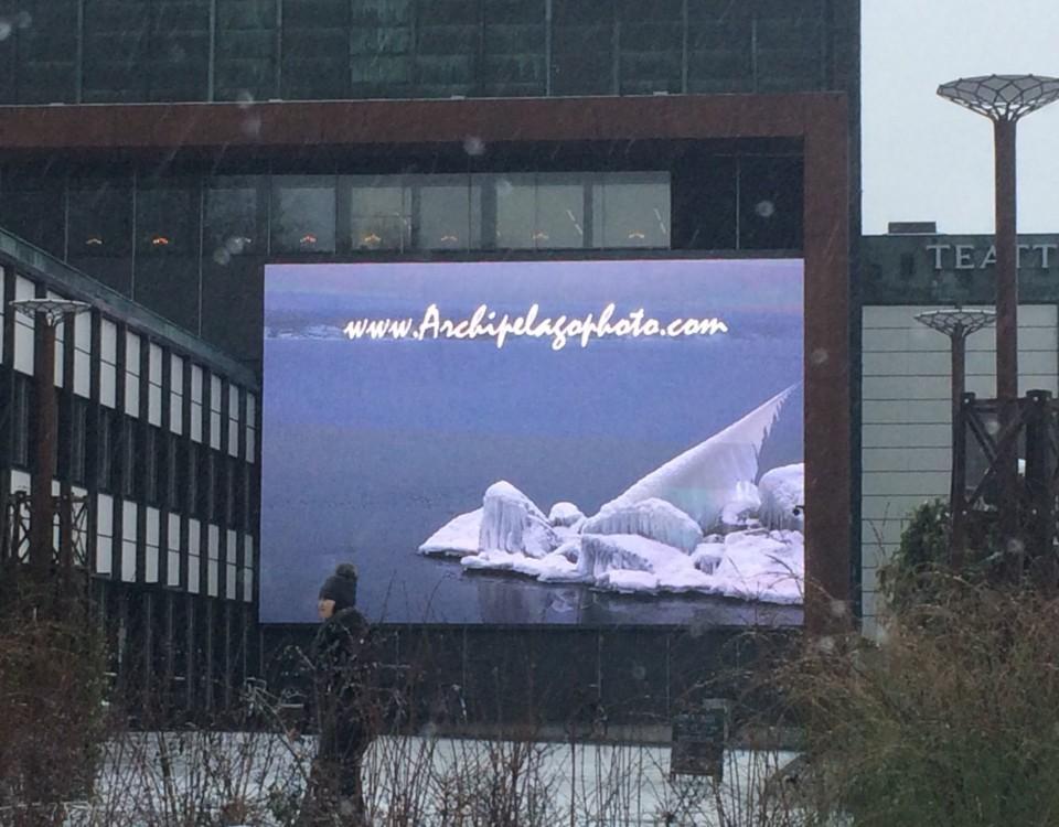 skärm på husvägg, på skärmen syns havsband vintertid