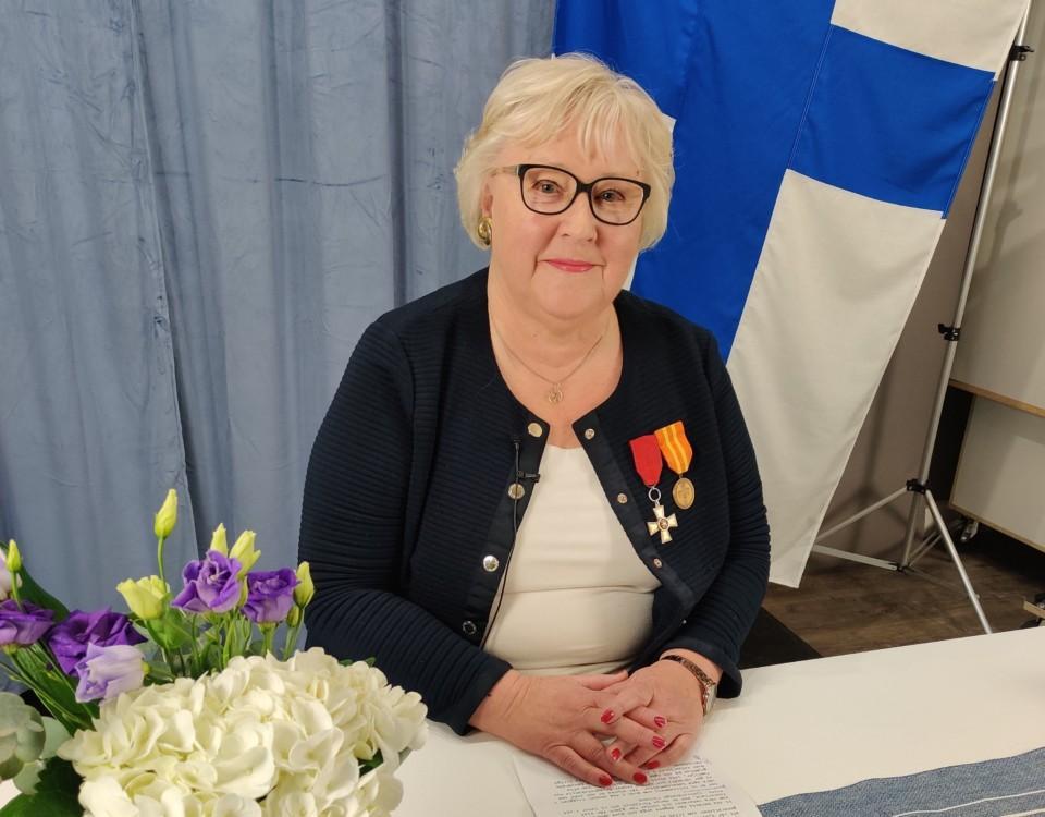 en kvinna framför Finlands flagga