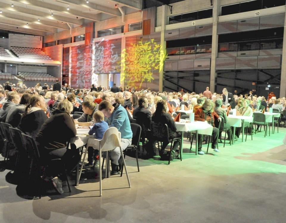 människor som sitter i en stor sal och äter tillsammans