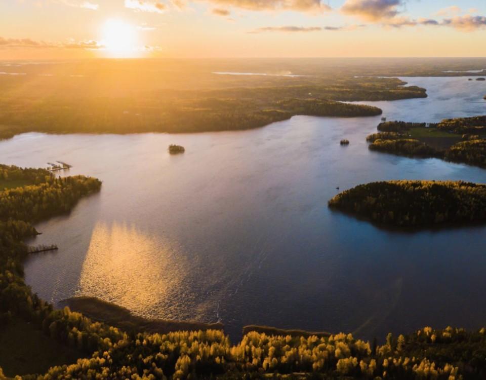 En solnedgång över sjöar och skogar.
