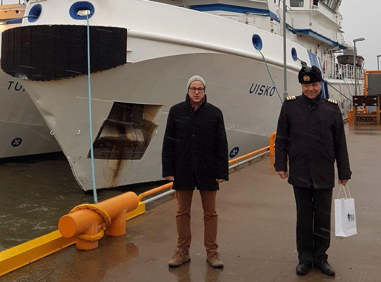 En sjökapten och en kommendör från gränsbevakningen på en fartygskaj