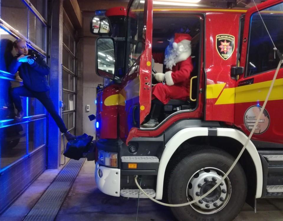 en man står på en brandbils kofångare och filmar julgubben i brandbilen
