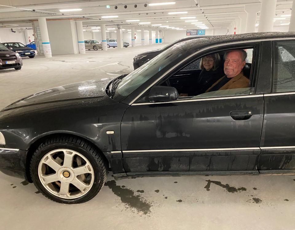 Par sitter i bil i parkeringshall