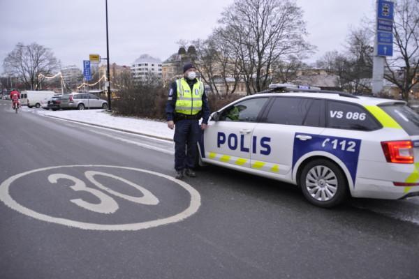 En polis står utanför en polisbil