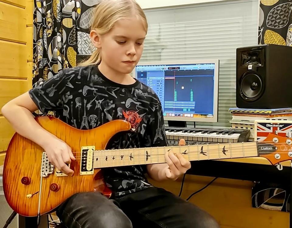 en ung pojke spelar gitarr
