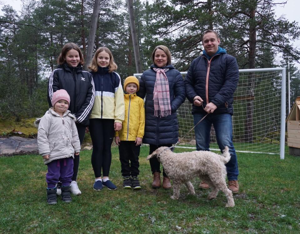 en familj med fyra barn och en hund står på en gräsmatta iklädda vinterkläder