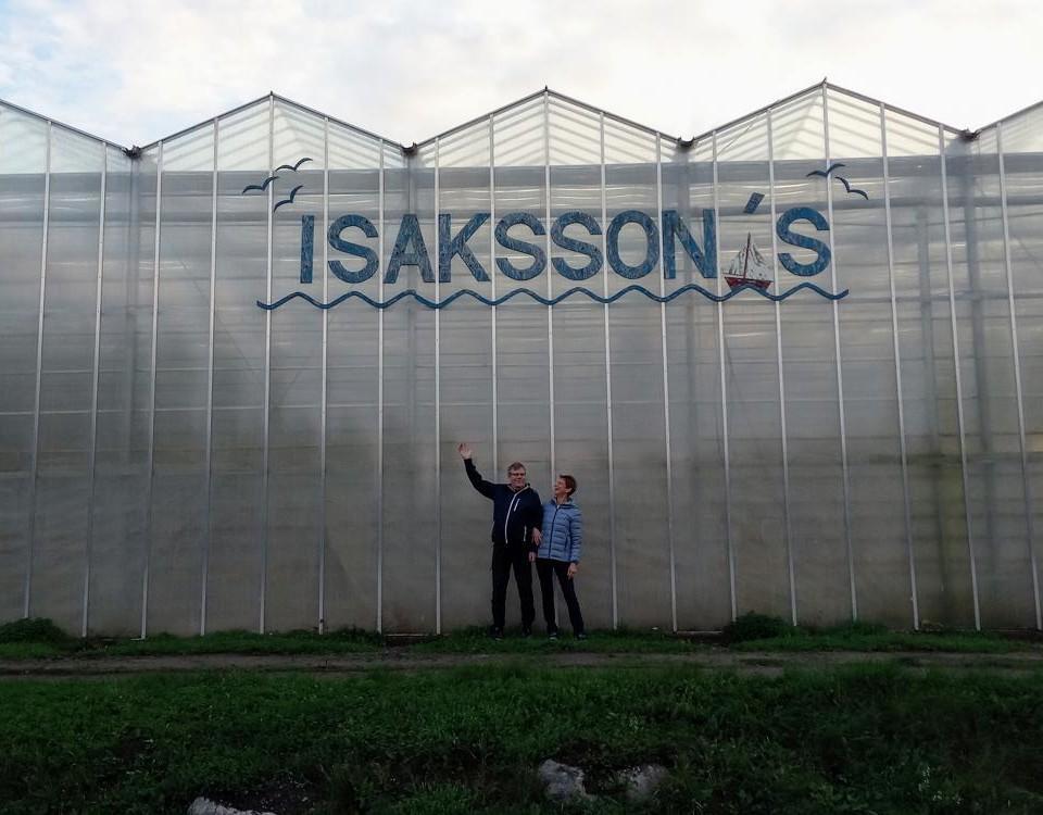 två personer framför stora växthus