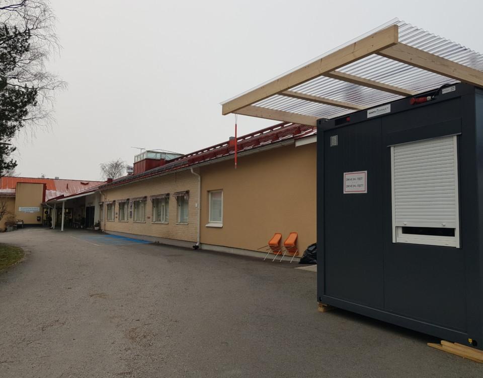 en låg hälsostationsbyggnad. I förgrunden en grå container märkt Drive in-test