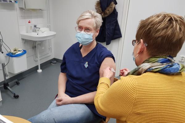 Dam i sjukvårdskläder blir vaccinerad
