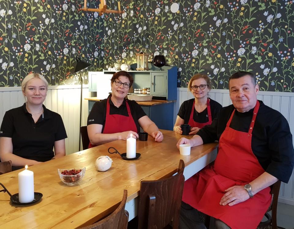 Restaurangkökspersonal har kaffepaus i rum med mörk tapet med blommor