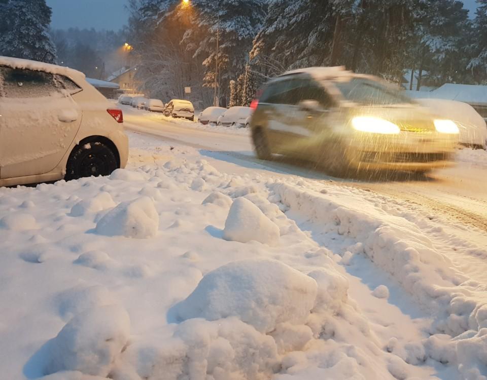 En bil som kör i snöyra med en snödriva i förgrunden.
