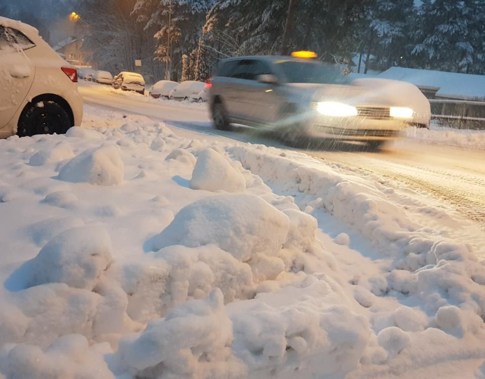 En taxibil som kör i snöyra med en snödriva i förgrunden.