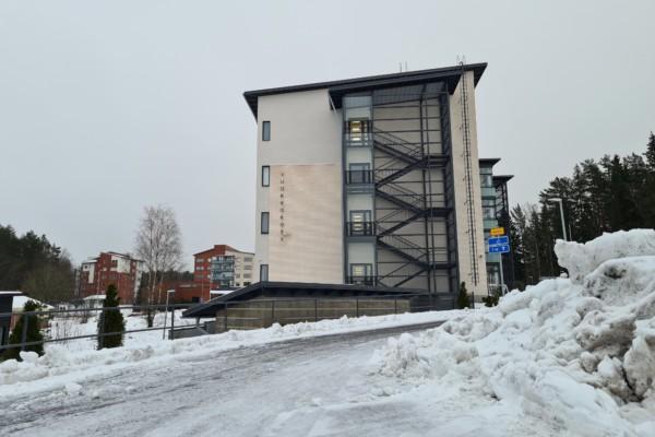 en hög byggnad vid slutet av en snöig väg