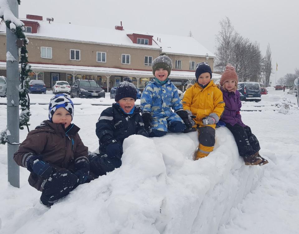 Fem barn i en snöhög på ett torg
