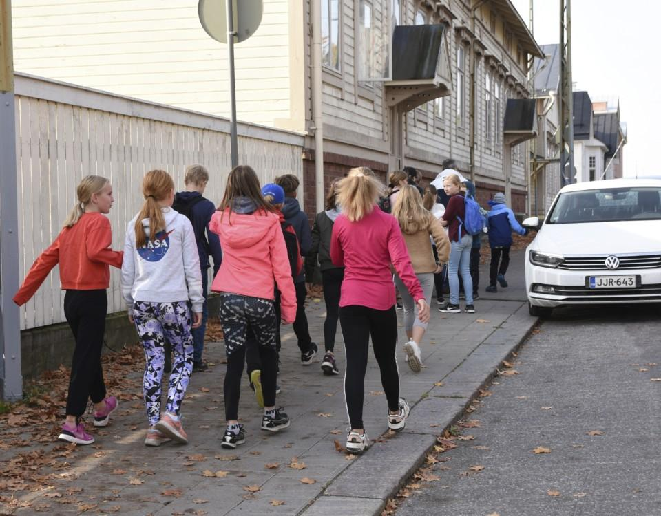 En grupp med barn går på trottoaren.