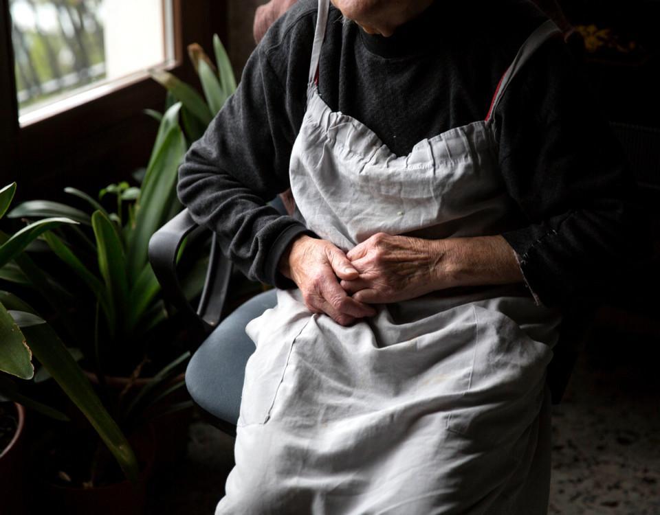 Äldre person sitter vid ett fönster.