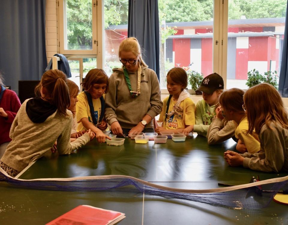 ett gäng scouter står samlade runt ett bord och pysslar med något.