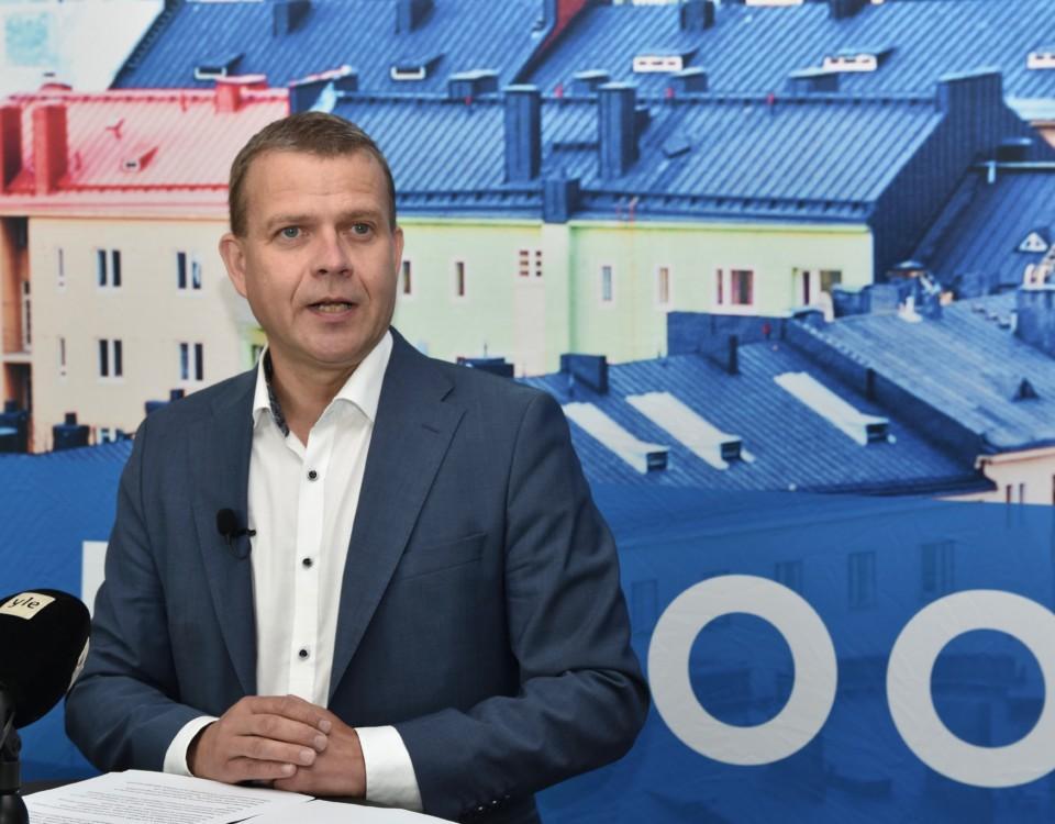 Samlingspartiets ordförande Petteri Orpo pratar framför journalisternas mikrofoner.