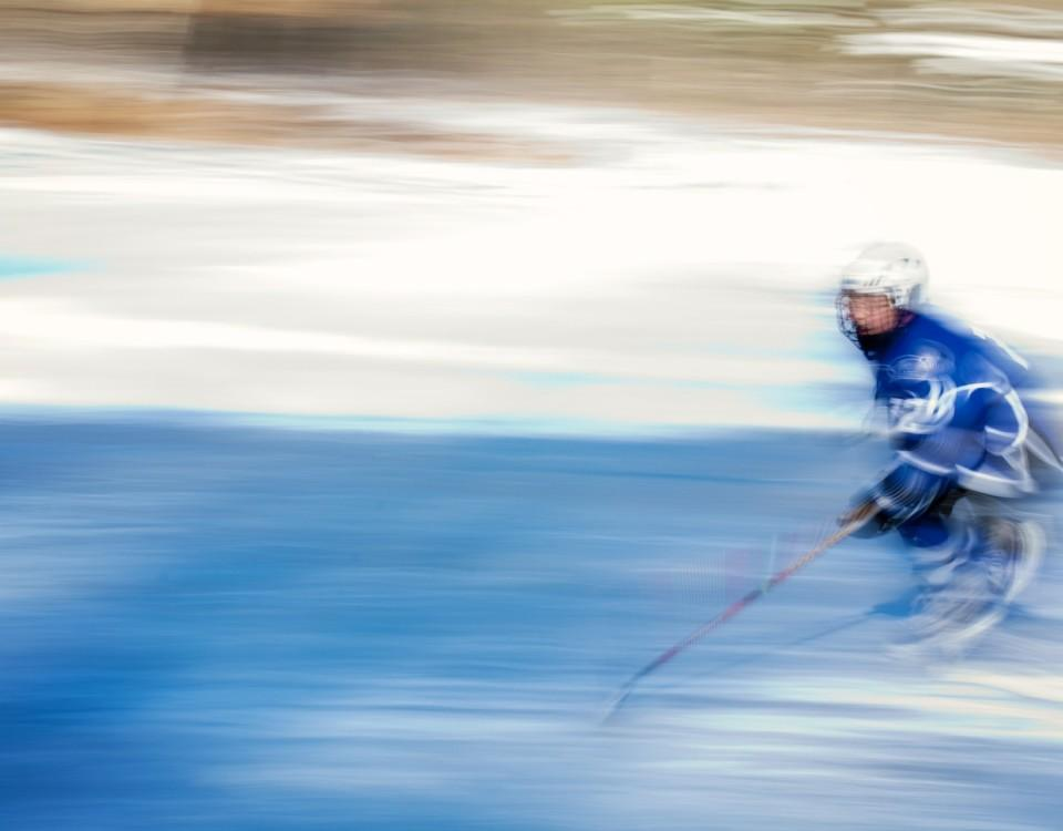 En ensam ishockeyspelare susar fram på isen.