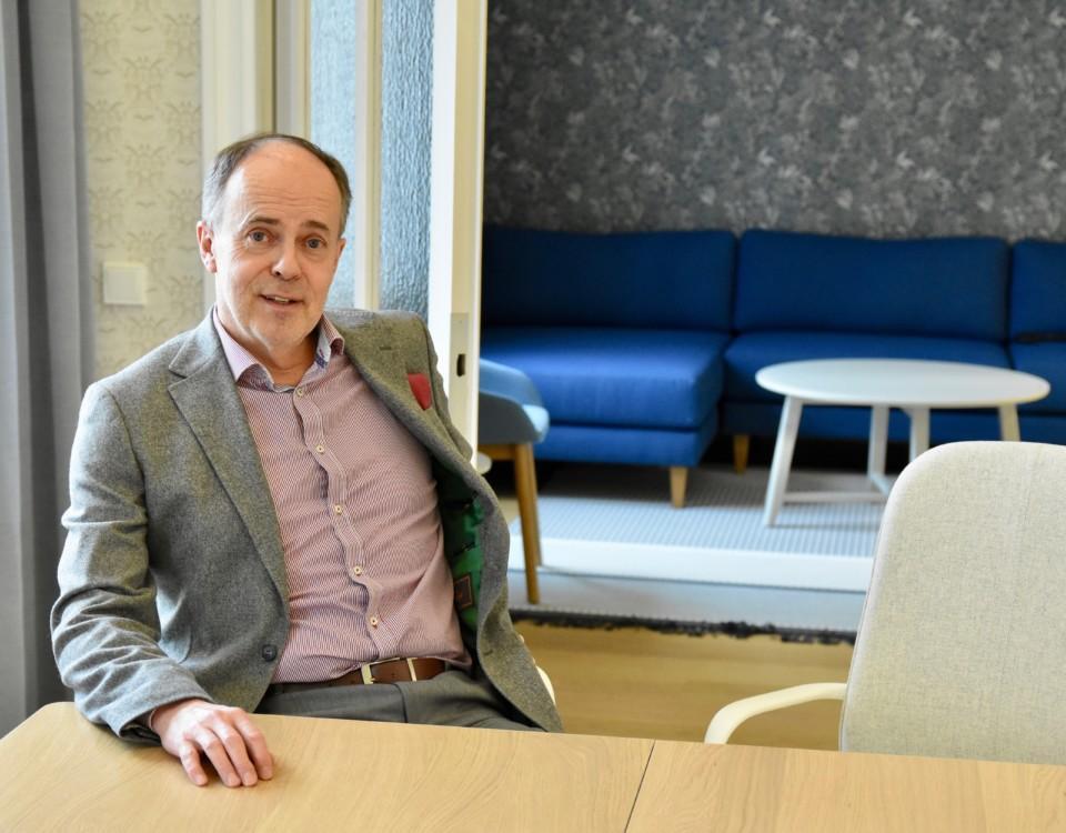 En man iklädd kostym sitter avslappnat tillbakalutad vid ett bord och tittar in i kameran.