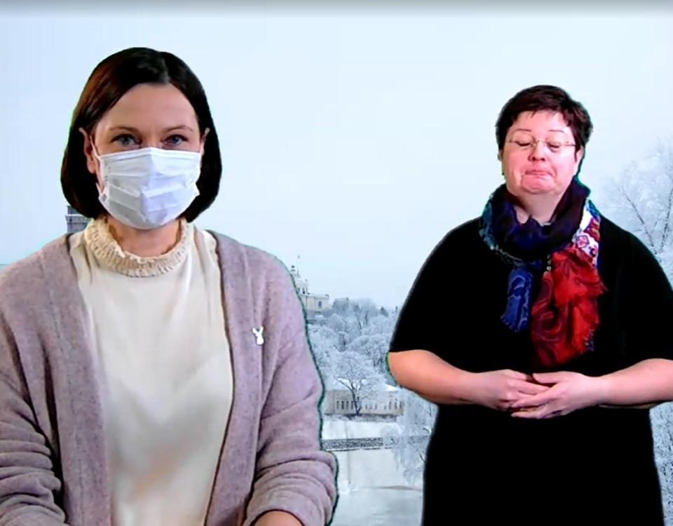 Minna Arve med munskydd, med en teckenspråkstolk i bakgrunden.