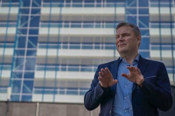 en man i kavaj framför en sjukhusbyggnad