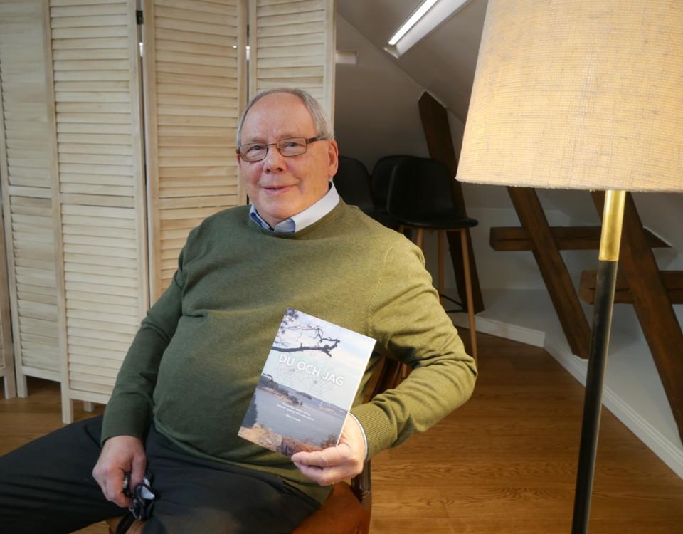 En äldre man håller upp en bok.
