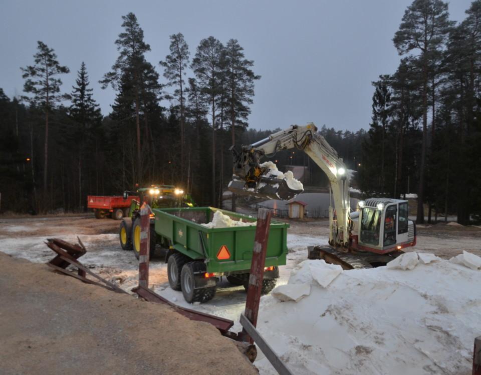 en grävskopa lastar ett traktorsläp med snö