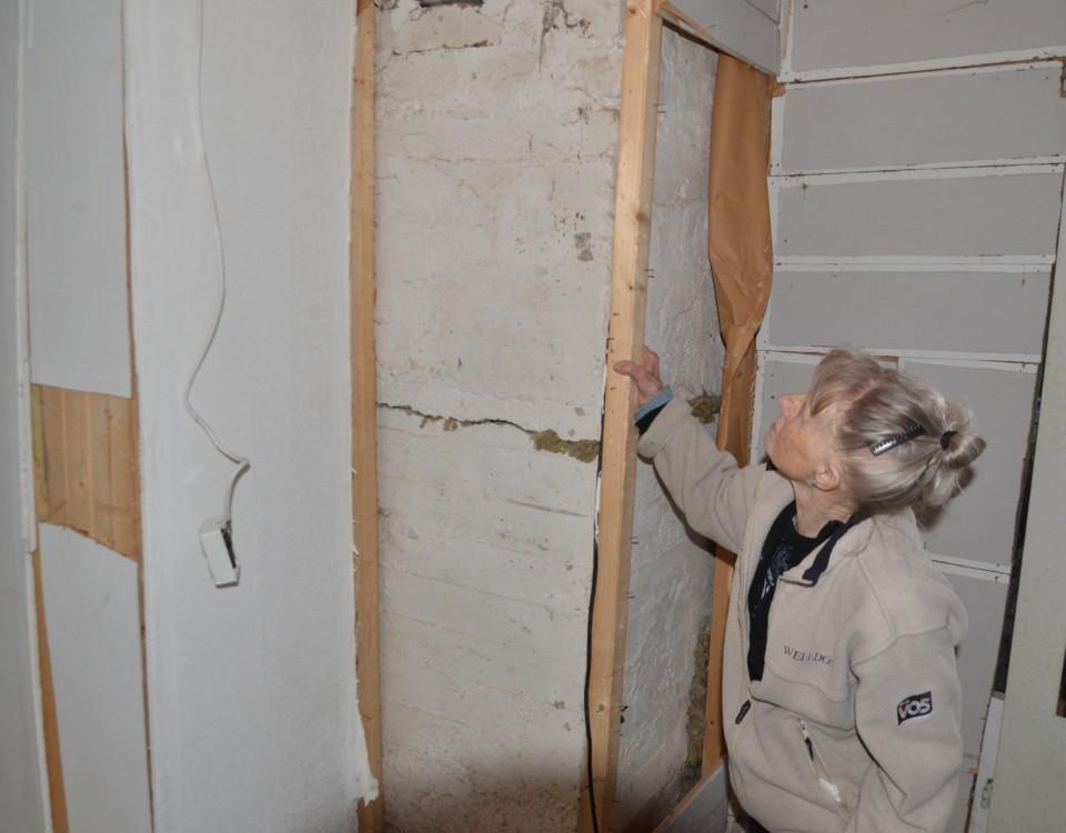 en kvinna inspekterar skador i konstruktionerna på en byggnad