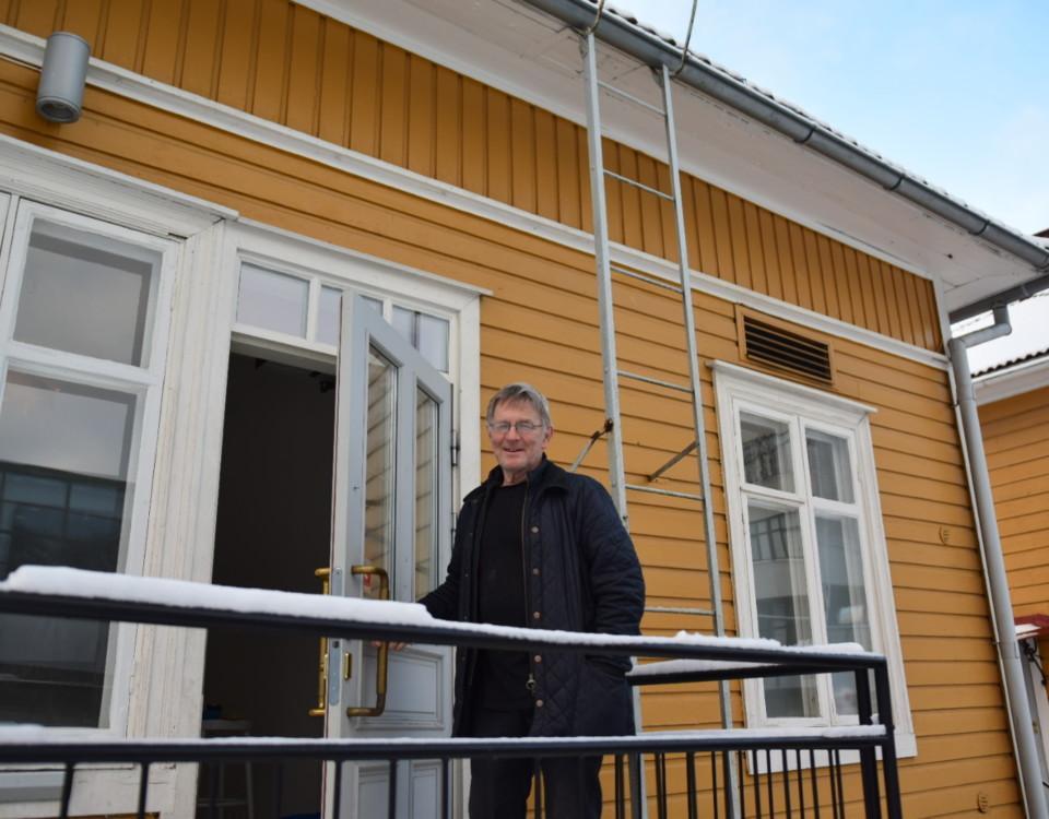 en man står på en trappa till ett gult trähus