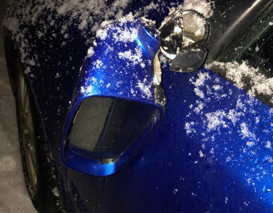 Trasig sidospegel på blå bil