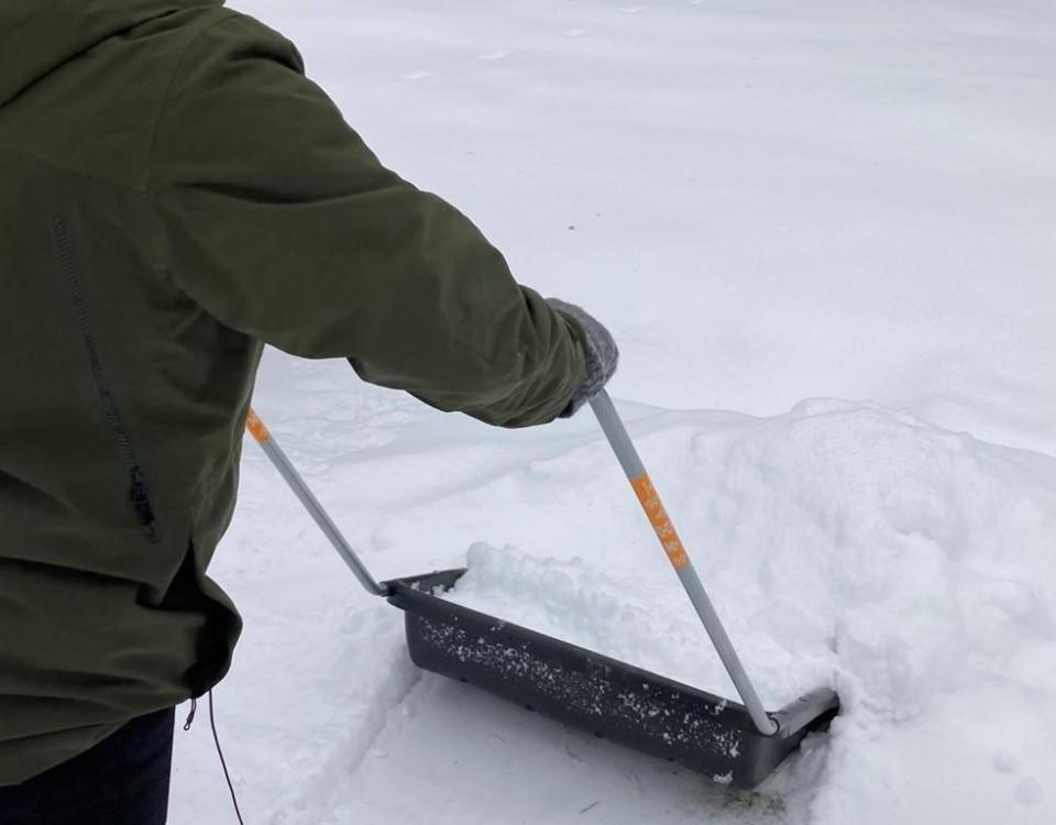 en person skottar snö